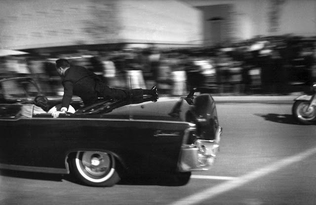 Seconds after shots rang out, the limousine carrying the mortally wounded President John F. Kennedy races toward the hospital in Dallas, Texas, on November 22, 1963. Secret Service agent Clinton Hill is riding on the back of the car, Nellie Connally, wife of Texas Gov. John Connally, bends over her wounded husband, and first lady Jacqueline Kennedy leans over the president.