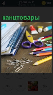 На поверхности стола лежат канцтовары, такие как тетрадь, скрепки, ножницы