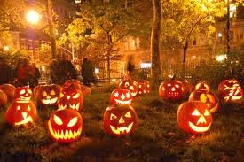 Carved pumpkins with scary faces and lights inside all sitting on a lawn at night