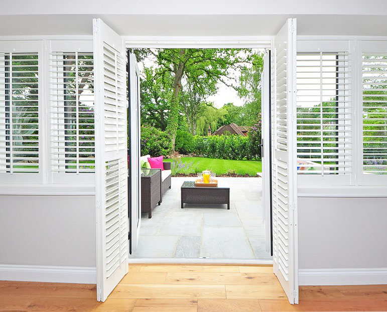 white wooden plantation shutters opening up to a sunny back garden