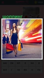 по улице идет девушка с сумками после шоппинга