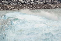 Ocean water is pushed up by the bottom of a pinnacle iceberg as it falls back during a large calving event at the Helheim glacier near Tasiilaq, Greenland, June 22, 2018. (Credit: Reuters/Lucas Jackson/File Photo) Click to Enlarge.