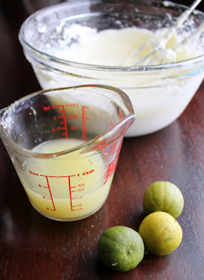 key limes next to measuring cup of key lime juice with bowl of whipped cream cheese in background