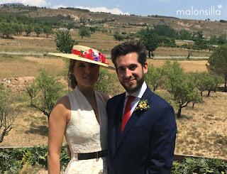 Canotier de ala ancha, look invitada boda en crudo y complementos en rojo