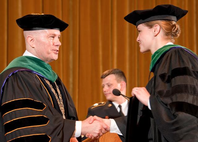 President Thomas shakes a graduate's hand