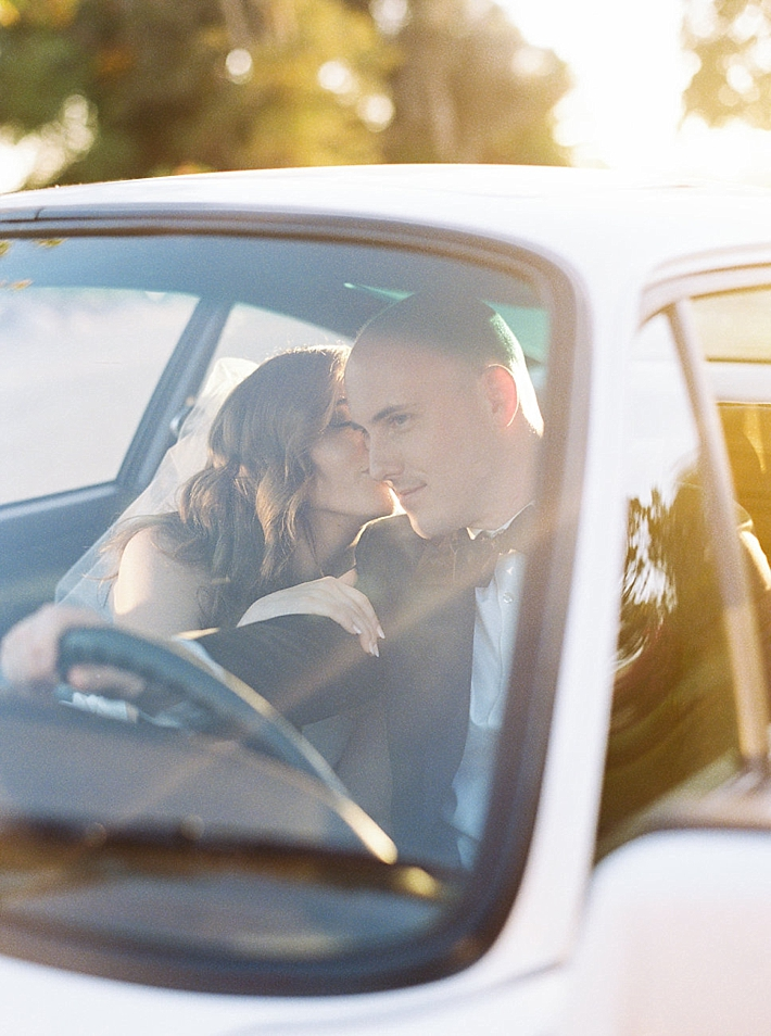 Bride kissing groom inside vintage white car | Photo by Matoli Keely Photography