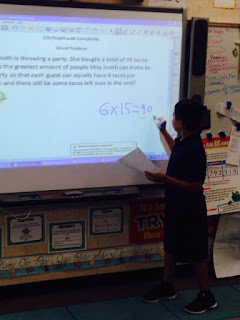 A student presents his math division strategy to the class.