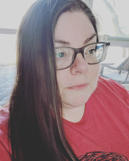 image of me in a red t-shirt and grey-framed glasses, with my hair down, watching the television in 3/4 profile