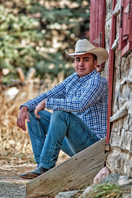 A young man dressed in rugged western wear and a cowboy hat poses infront of a weathered log cabin for his senior portraits in Golden Colorado