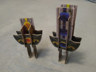 Two of the hilts, each with some tiles placed onto it. The one on the left has only three tiles, so two are connecting the crossguard pieces and only one is above the actual crossguard. The one on the right, however, has eight total tiles, so two above each crossguard, and two on each of the other two sides. On this one, all three of the tiles (both the two normal tiles and the crossguard) facing the camera have blue gems on them.