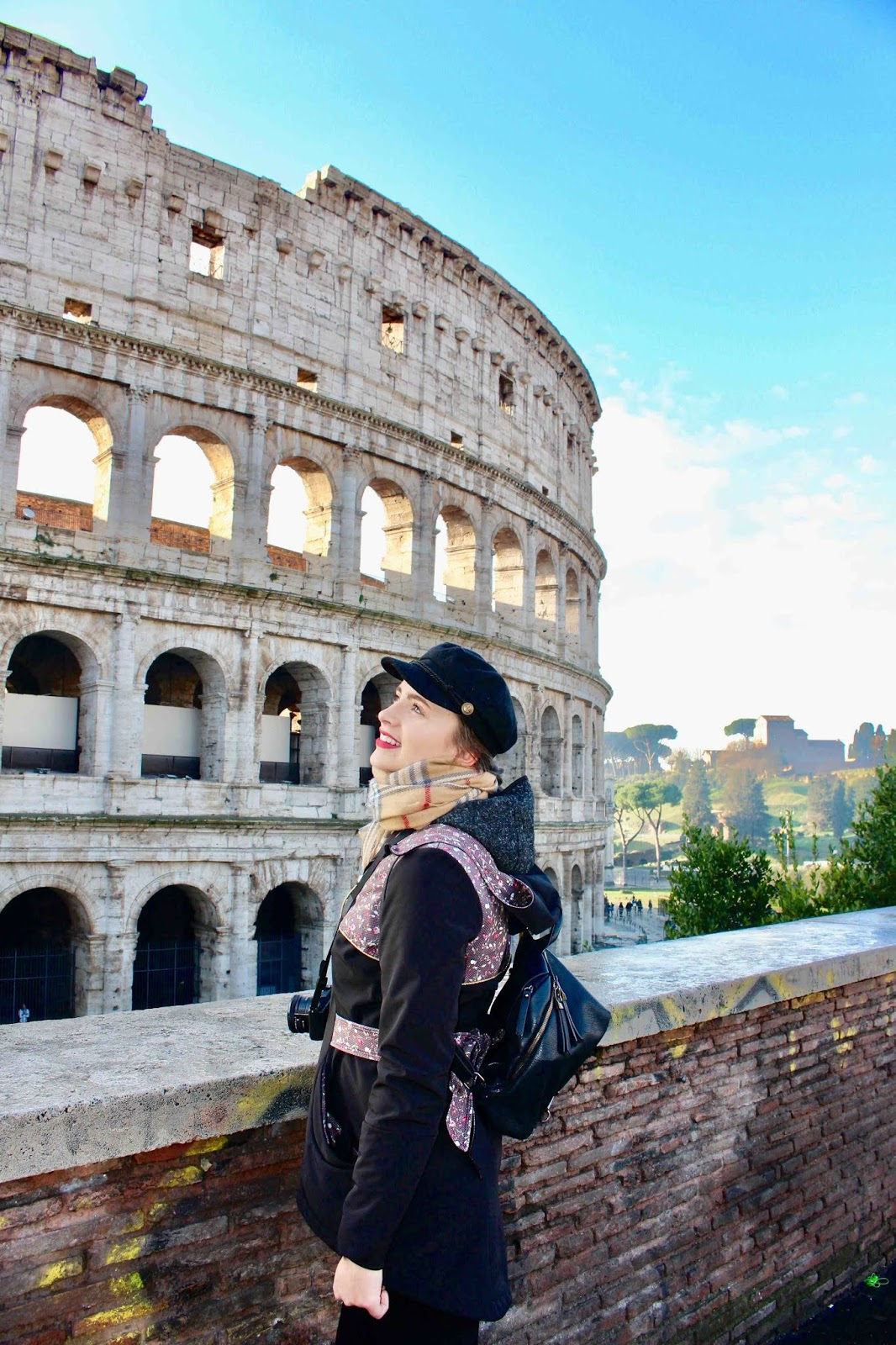 Girl in front of Colosseum with camera and blue sky in background