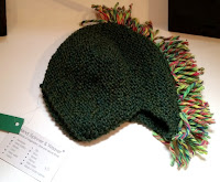 Dark green helmet shaped hat with multicoloured fringe in a mohawk style.