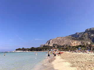 Mondello's beautiful sandy beach is largely free to use and attracts crowds of bathers in high season