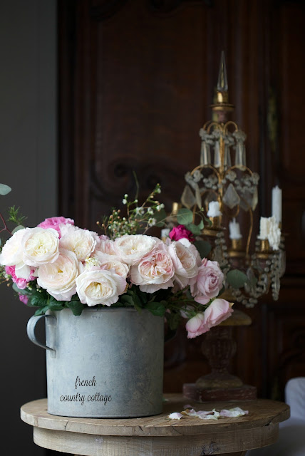 Bucket of garden roses with candle chandelier