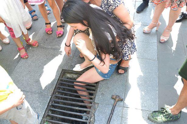 Jovem caminha digitando no celular e fica presa em bueiro