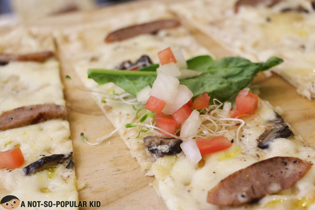 The panizza is served with alfalfa sprouts and arugula leaves - Torch Restaurant