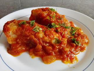 Bacalao frito con sofrito de tomate y perejil picado por encima