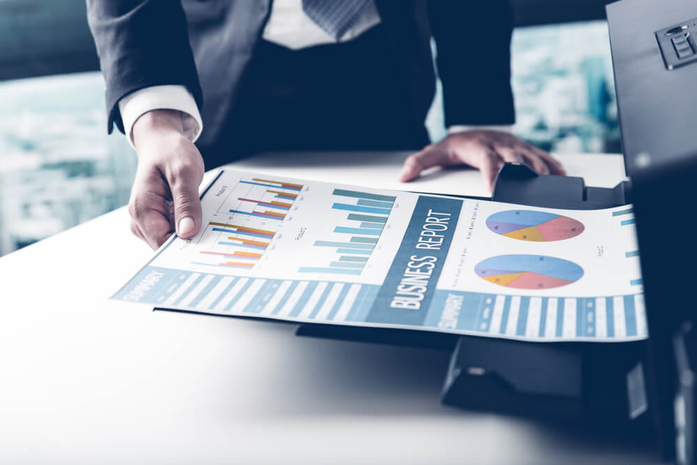 Businessman pulling out printed graphs and charts used for analysis