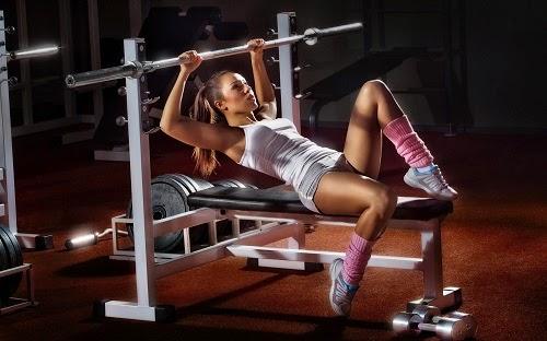 Chica fitness haciendo press banca en el gimnasio