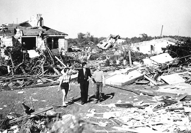 Elected to the U.S. Senate in 1952, here, Senator John F. Kennedy, accompanied by Dick Mayer, 15, and Melissa Tyler, 14, of Shrewsbury, Massachusetts inspects tornado damage in Shrewsbury, on June 10, 1953. At least 86 were left dead in the area by the tornado, 800 injured and 2,500 made homeless.