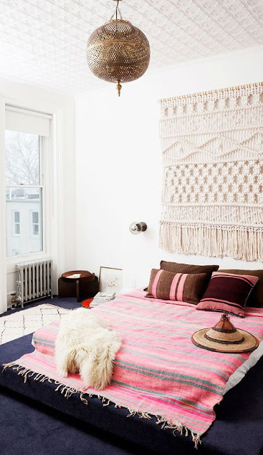 boho chic bedroom with a pink woven rug and large macrame