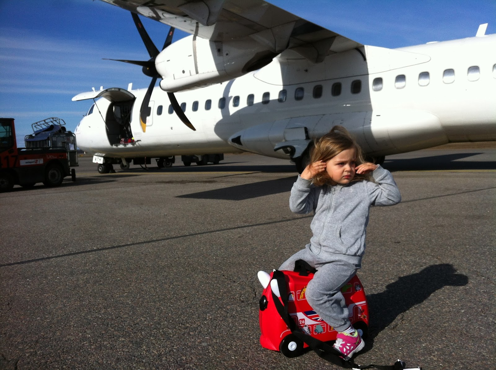 toddler sitting on trunki rideon suitcase in front of a plane