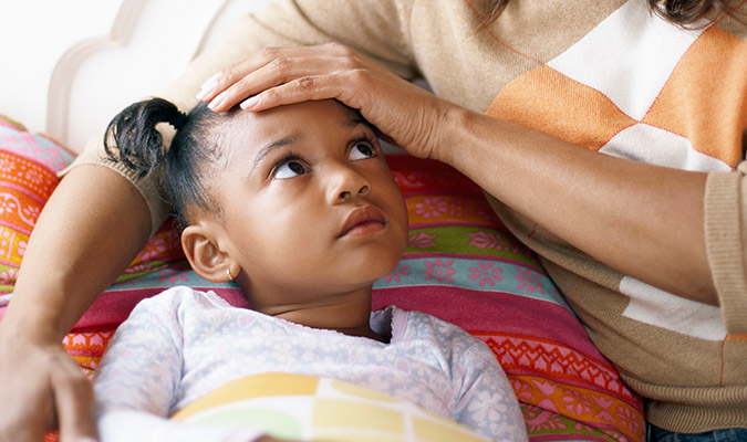 Mother feeling sick child's forehead to check for fever