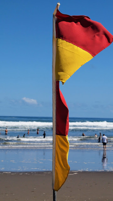 Red and yellow flag on Piha Beach near Auckland New Zealand