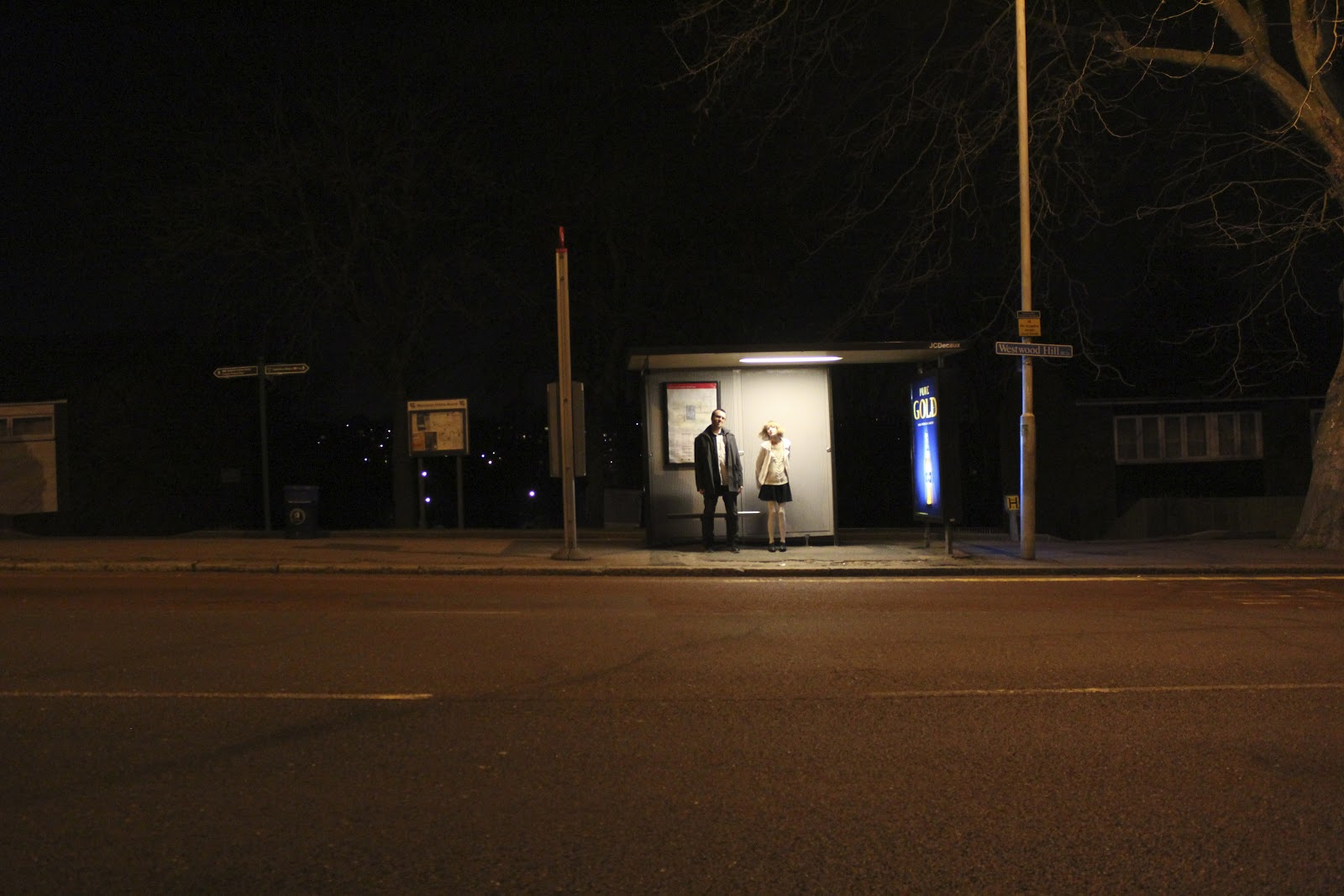 A man and woman standing up straight at a bus stop. Long shot.