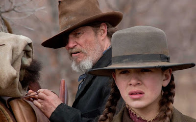 Jeff Bridges as Rooster Cogburn looking at Hailee Steinfeld as Mattie Ross