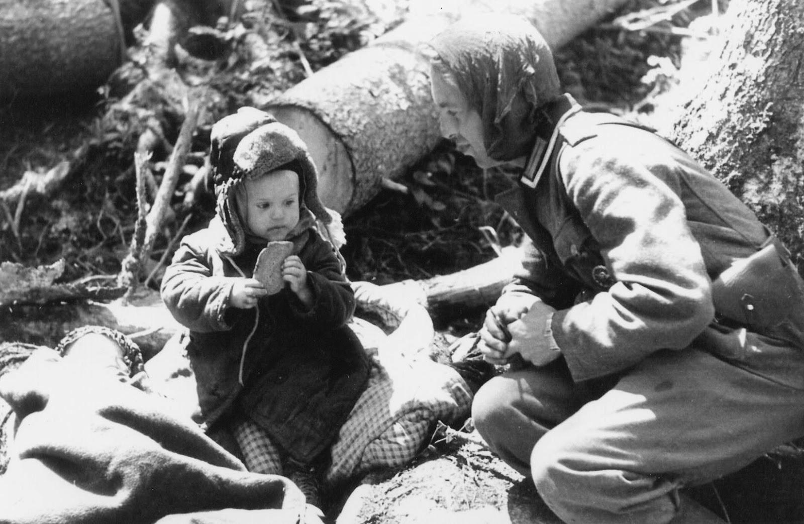 Soldado alemán dando pan a un niño ruso huérfano. Área de Volkhov, 1942