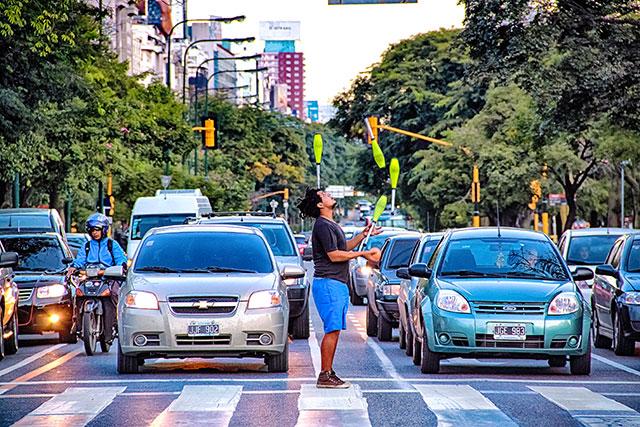 En un corte de semáforo un joven hace malabares con clavas