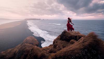 Chica vestida de roja sintiendo el viendo en la cima de una montaña con el mar de frente