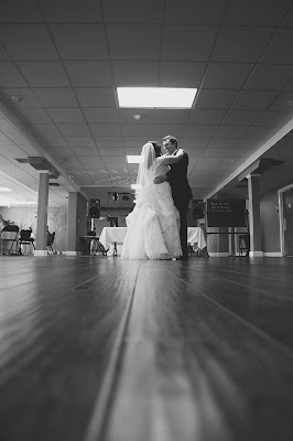 B&W photo of a masc in a suit and femme in a wedding dress dancing