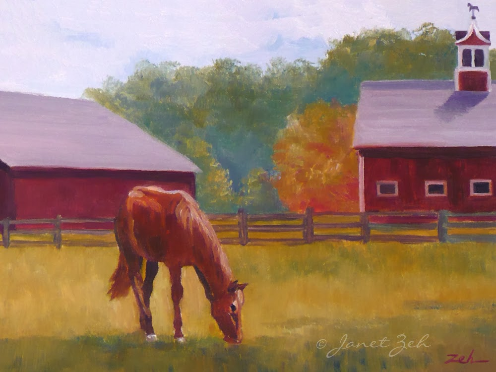 A horse grazes in a field by a red barn