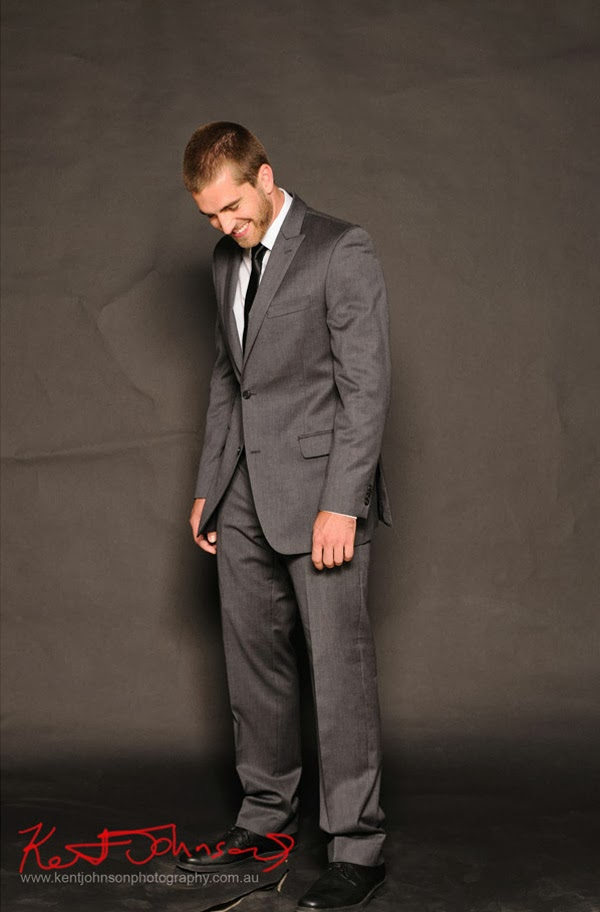 Casual character studio shot full length, men's fashion photography - Evan in a grey suit laughing - Photographed by Kent Johnson.
