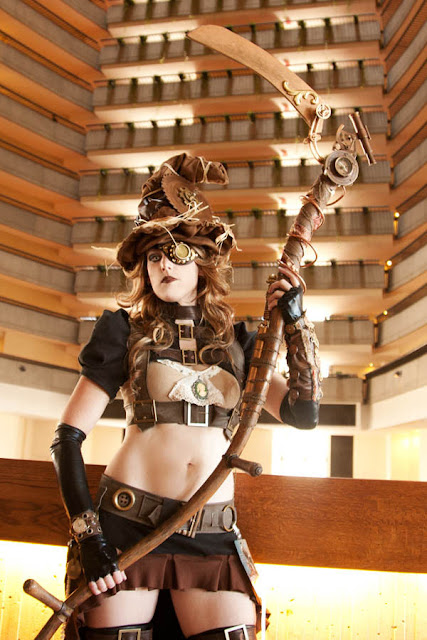 Women's steampunk halloween costume ideas. Steampunk witch with witches hat, eyepatch, scythe instead of broom, skirt and harness.