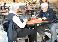 Elderly couple seated at a food court table talking on cell phones