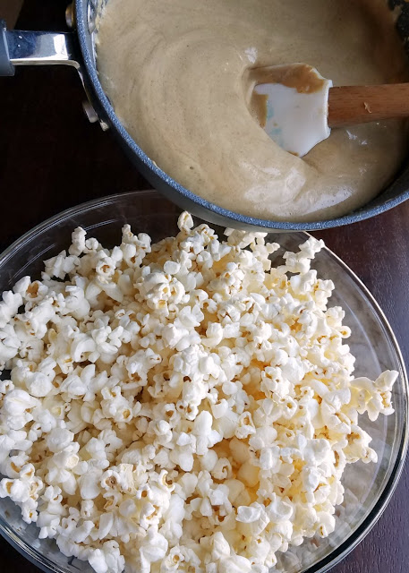pouring peanut butter caramel mixture over bowl of popcorn