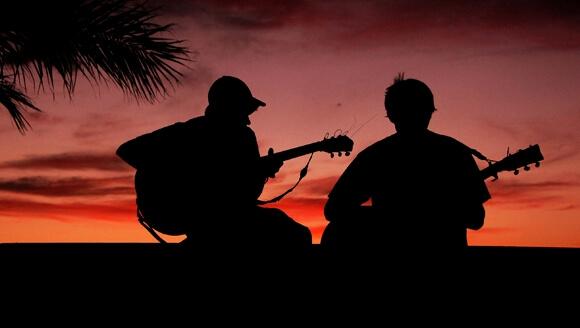 Silueta de personas tocando guitarra