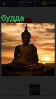 В свете вечернего заката большая фигура будды расположена на холме, вокруг только проплывающие облака