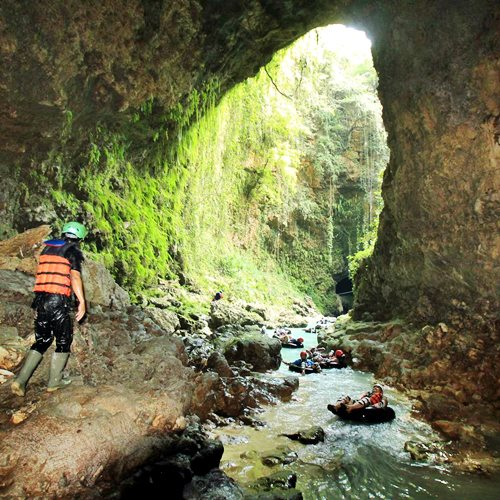 Tinuku Travel Kalisuci cave tubing, down underground river in karst cave system landscape Sewu Mountains Geopark