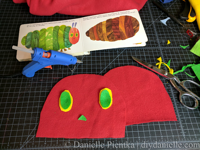 Using a hot glue gun to apply pieces to hat.