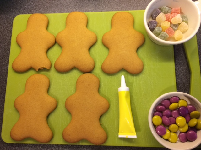 Gingerbread men laid out on a chopping board with a tube of icing and sweets in bowls