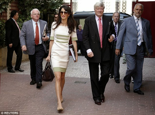 Amal Alamuddin heads to a meeting in a chic green and white midi dress in Athens