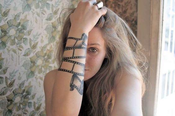 Chica rubia con tatuaje de un film de pelicula a modo de brazalete