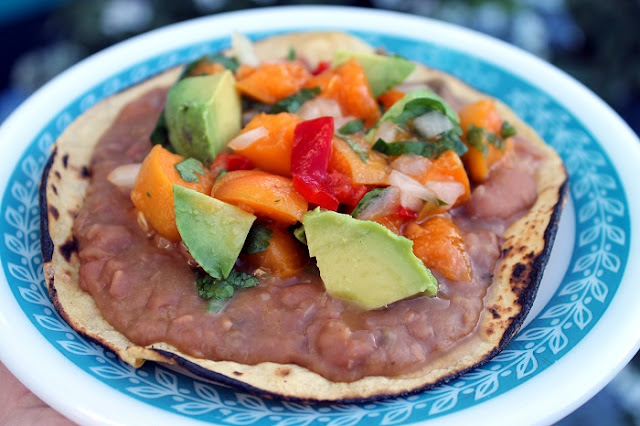 Creamy dreamy pinto beans on a toasted corn tortilla with avocado and fresh apricot salsa.