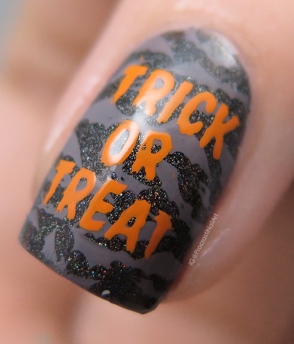 Bats and trick or treat lettering stamped over a black holographic nail polish