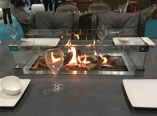 Pic of fire in centre of table with glasses, plates and another table and chairs in background