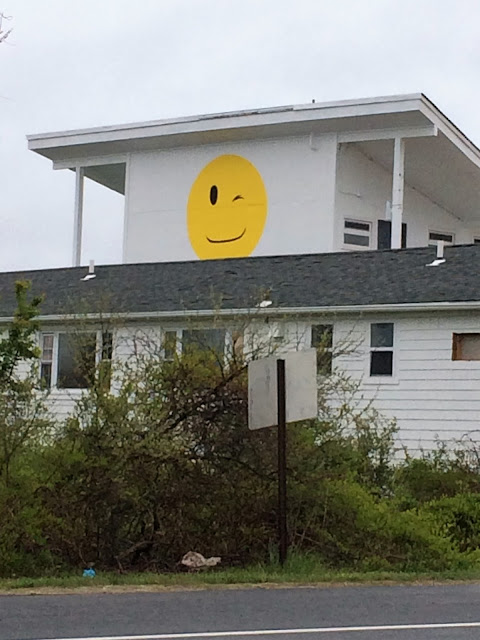 Two story white building with a large winking emoji painted on the side